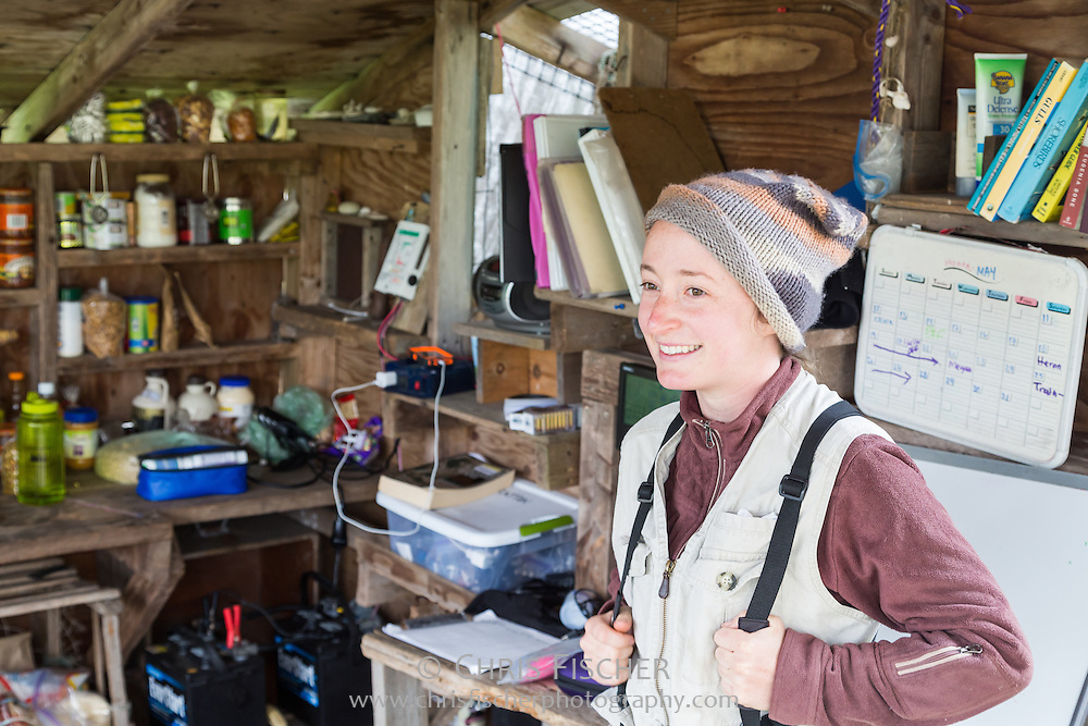 Emily Pollom, Stratton Island Supervisor for National Audubon Society's Seabird Restoration Program, taking a moment of downtime in the outdoor kitchen at basecamp. (The batteries and wires viewable in the background are part of a photovoltaic solar system which powers research equipment, including laptops and cell phones.)