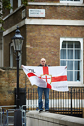© Licensed to London News Pictures.  20/09/2014. LONDON, UK. A member of the English Defence League (EDL) holds a flag opposite Downing Street. The group is attempting to highlight it belief that  Muslim sexual grooming gangs are abusing English girls. Earlier this week a home office official warned of the rise of the far right. Photo credit: Cliff Hide/LNP