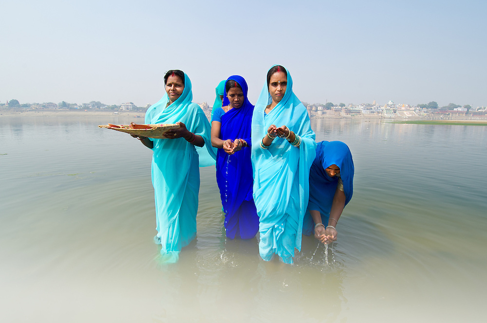 Women wearing blue coloured sarees performing a morning religious ritual ('puja') while standing in river Ganga (Ganges), Varanasi (India)