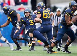 Nov 7, 2015; Morgantown, WV, USA; West Virginia Mountaineers quarterback Skyler Howard is tripped up as he runs up the middle against the Texas Tech Red Raiders during the first quarter at Milan Puskar Stadium. Mandatory Credit: Ben Queen-USA TODAY Sports