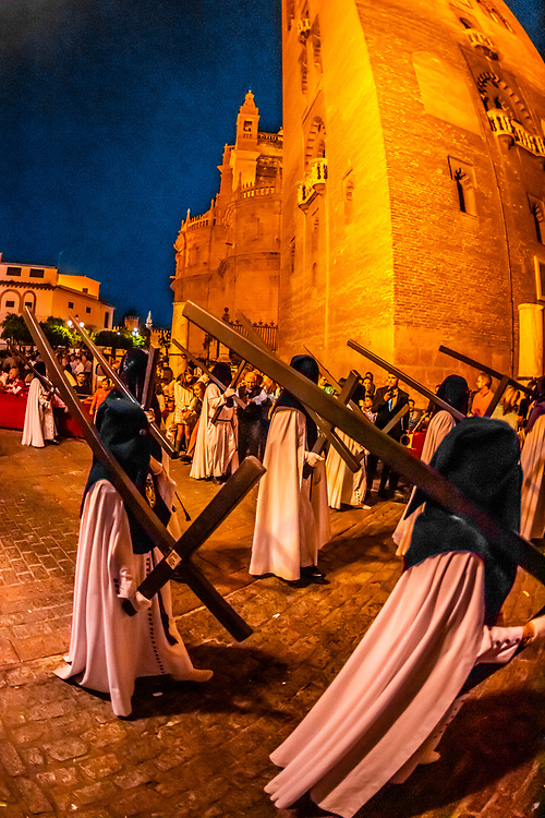 Hooded Penitents (Nazarenos) in the procession of the Brotherhood (Hermandad) San Benito carrying crosses, Holy Week (Semana Santa), Seville, Andalusia, Spain.