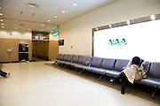 Narita airport passenger hallway with row of chairs and person sleeping
