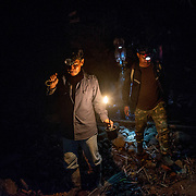 Honey hunters using head lamps and carbide lamp to light inside the forest. Climbing the Tualang tree and harvesting honey are done during night, when the giant honey bee are calmer and more docile.