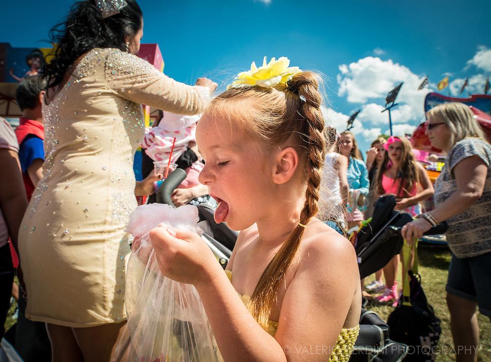 A girl attacks her pink candyfloss bag. Candyfloss is a children's evergreen.