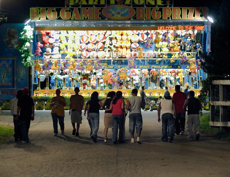 Mechanicstown, N.Y. - People walk toward a brightly lit arcade game at the Orange County Fair on July 29, 2006. ©Tom Bushey