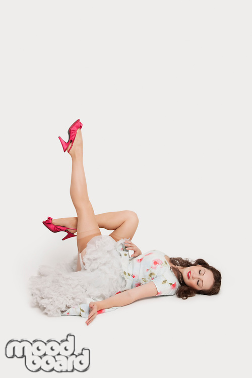 Beautiful young woman in dress lying on floor with feet up against white background