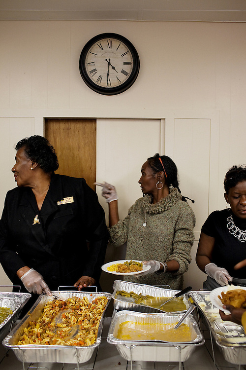 "Vickie Wooten (middle) helps serve food at the gathering after the funeral of Demetrius ""Butta"" Anderson, 18, at McKinney Chapel in the Baptist Town neighborhood of Greenwood, Mississippi on Friday, November 5, 2010. Wooten also happens to be raising three children while her husband is in prison."
