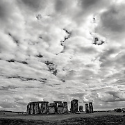 Stonehenge Monochrome with Stark Clouds. Believed to have been built somewhere between 2000 and 3000 BC, Stonehenge is one of the United Kingdom's most distinctive landmarks. It's function and purpose remains a matter of conjecture, although many theories have been offered. It consists of a series of large standing stones, some of which have toppled over the centuries. Stonehenge is located in Salisbury Plain west of London.