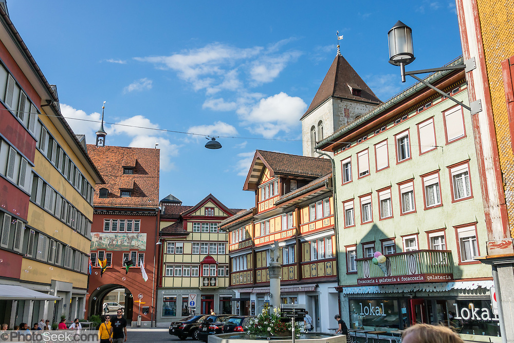 In Appenzell village, the red Rathaus (built 1560-83) houses the city hall, Appenzell Museum (in attached yellow building), tourist office and library, on Hauptgasse (Main Street), in Switzerland, Europe. The Rathaus facade mural was painted by August Schmid from Diessenhofen (1928). Appenzell Museum shows a cross section of the Swiss Canton's history and culture (1400s flags and banners, embroidery, folk art, and even historic torture instruments). Appenzell village is in Appenzell Innerrhoden, Switzerland's most traditional and smallest-population canton (second smallest by area).