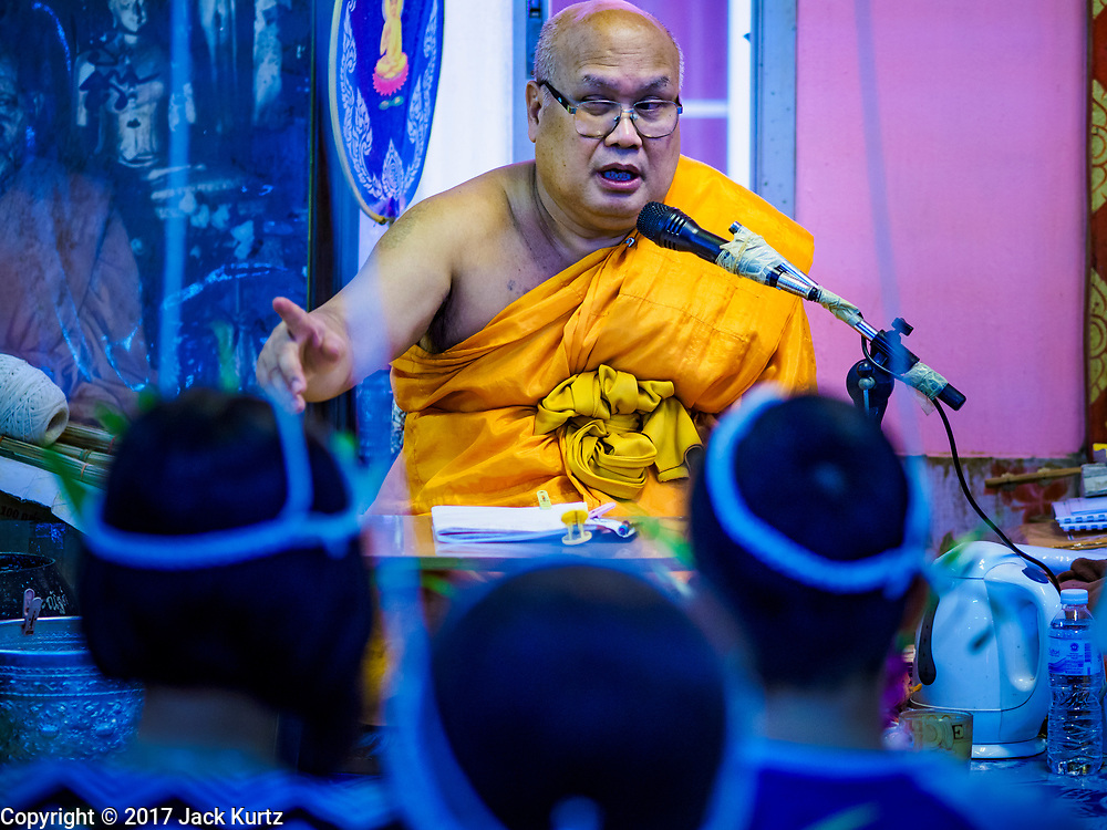 """24 JUNE 2017 - BANG KRUAI, NONTHABURI: A Buddhist monk preaches during a """"resurrection"""" or rebirthing ceremony at Wat Ta Kien (also spelled Wat Tahkian), a Buddhist temple in the suburbs of Bangkok. People go to the temple to participate in a """"Resurrection Ceremony."""" Thai Buddhists believe that connecting people by strings around their heads, which are connected to a web of strings suspended from the ceiling, amplifies the power of the prayer. Groups of people meet and pray with the temple's Buddhist monks. Then they lie in coffins, the monks pull a pink sheet over them, symbolizing their ritualistic death. The sheet is then pulled back, and people sit up in the coffin, symbolizing their ritualist rebirth. The ceremony is supposed to expunge bad karma and bad luck from a person's life and also get people used to the idea of the inevitability of death. Most times, one person lays in one coffin, but there is family sized coffin that can accommodate up to six people. The temple has been doing the resurrection ceremonies for about nine years.     PHOTO BY JACK KURTZ"""