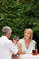 Couple toasting with wine glasses sitting outdoors