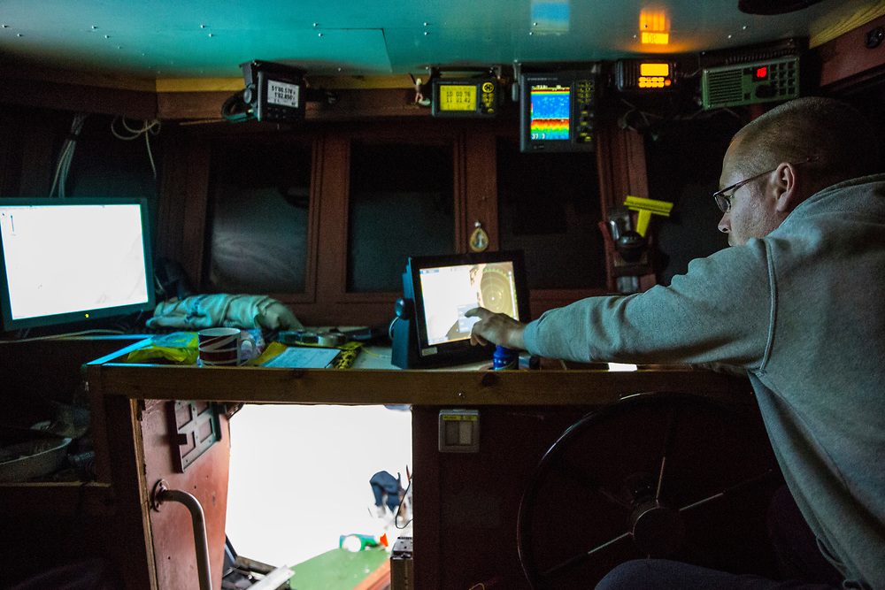 Luke checks the sonar to make sure he is avoiding major objects on the sea bed while his nets are down trawling for fish. Luke is a Folkestone based fisherman out trawling solo for a regular 12 hour night shift on a fishing trip in his boat Valentine (FE20), Hythe Bay, the English Channel, United Kingdom. (photo by Andrew Aitchison / In pictures via Getty Images)