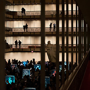 February 12, 2015 - New York, NY : Patrons of the New York City Ballet view artist Dustin Yellin's 'Psychogeographies,' a set of 15 sculptural collages/paintings in the David H. Koch Theater at Lincoln Center on Thursday evening during a party following the evening's performance.  DJ Gaspar, visible at right, entertains the crowd. Yellin made the works for New York City Ballet's 2015 Art Series. CREDIT: Karsten Moran for The New York Times