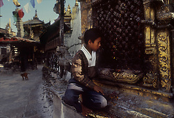KATHMANDU, NEPAL - OCTOBER 1992 - A Nepalese boy reaches for coins tossed for good luck by tourists at the Monkey Temple in Kathmandu. (PHOTO © JOCK FISTICK)