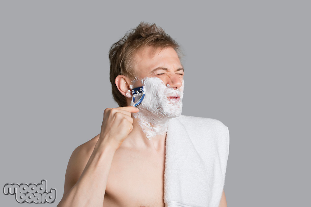 Young man shaving while making faces with eyes closed over colored background