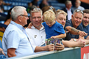 AFC Wimbledon fan reading programme during the EFL Sky Bet League 1 match between AFC Wimbledon and Wycombe Wanderers at the Cherry Red Records Stadium, Kingston, England on 31 August 2019.