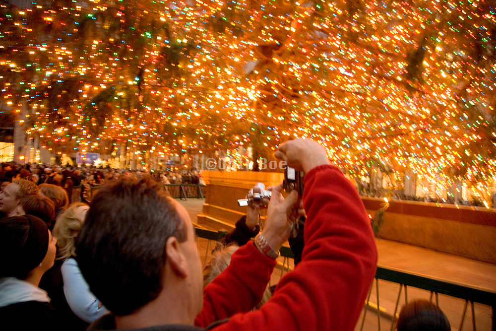 people gathering under the Rockefeller Center Christmas tree in New York
