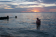 As the sun sets over fading daylight and calm waters of the Thames Estuary, a wild sea swimmer carefully walks out of the water after his regular evening dip, on 18th July 2020, in Whitstable, Kent, England.