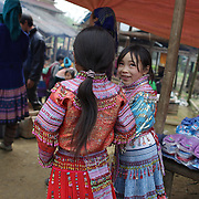 Young girls at the Lung Khau Nhin Market. Vietnam. Lung Khau Nhin Market is rural tribal market hiding itself amongst the mountains and forests of the far north Vietnam about 10 km from the border with China. The market plays an important role for the local ethnic people, Flower Hmong, Black Zao, Zay, and very small ethnic groups  Pa Zi, Tou Zi, Tou Lao. Tourist trips to the market run from Sapa and Lao Cai every week. Lung Khau Nhin Market, Vietnam.15th March 2012. Photo Tim Clayton