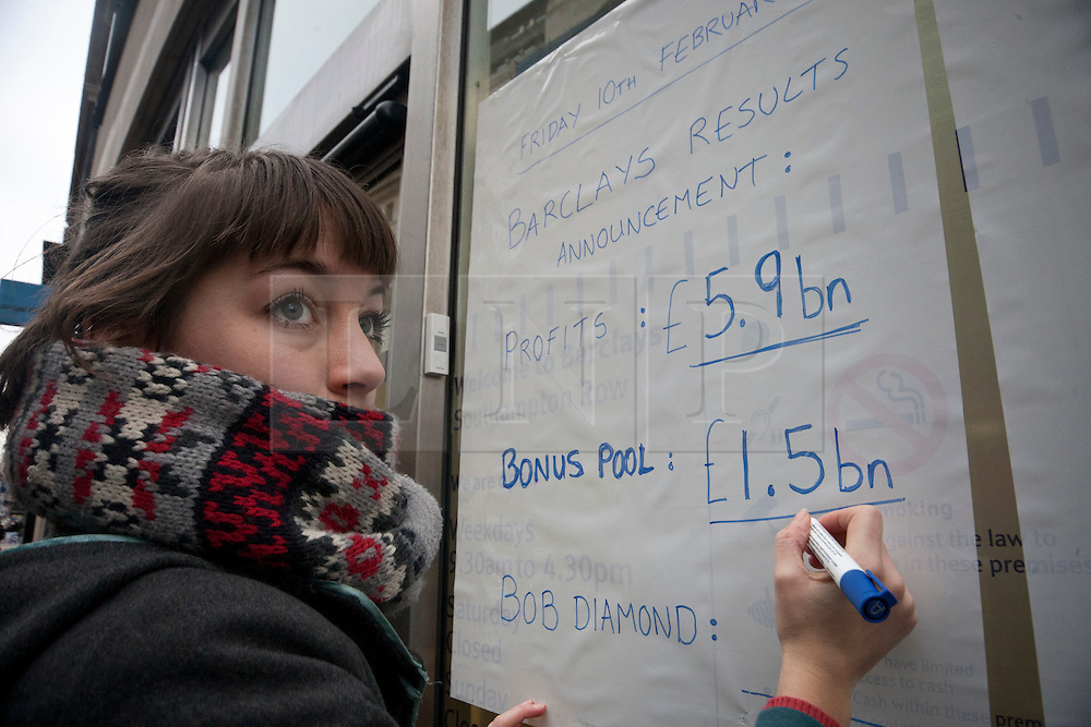 © licensed to London News Pictures. London, UK 10/02/2012. A protester writes the Barclays Bank profit and bonus results on the outside of a branch of Barclays Banks in central London on February 10th, 2012, during a protest in support of the 'Move Your Money UK' campaign. Barclays today (10/02/2012) announces its annual results. Photo credit: Tolga Akmen/LNP
