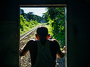 25 NOVEMBER 2017 - YANGON, MYANMAR: A passenger stands in the back of the Yangon Circular Train and watches the countryside roll by. The Yangon Circular Train is a 45.9-kilometre (28.5 mi) 39-station two track loop system connects satellite towns and suburban areas to downtown. The train was built during the British colonial period, the second track was built in 1954. Trains currently run both directions (clockwise and counter-clockwise) around the city. The trains are the least expensive way to get across Yangon and they are very popular with Yangon's working class. About 100,000 people ride the train every day. A a ticket costs 200 Kyat (about .17¢ US) for the entire 28.5 mile loop.    PHOTO BY JACK KURTZ