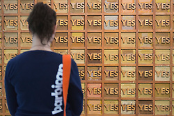"© Licensed to London News Pictures. 21/10/2013. London, England. A museum workers stands in front of the artwork Joe Tilson, Page 1, 1969.  The Exhibition ""Pop Art Design"" opens at the Barbican Art Gallery/Barbican Centre running from 22 October 2013 to 9 February 2014. The exhibition brings together 200 works by 70 artists and designers including Peter Blake, Andy Warhol and Roy Lichtenstein. Photo credit: Bettina Strenske/LNP"
