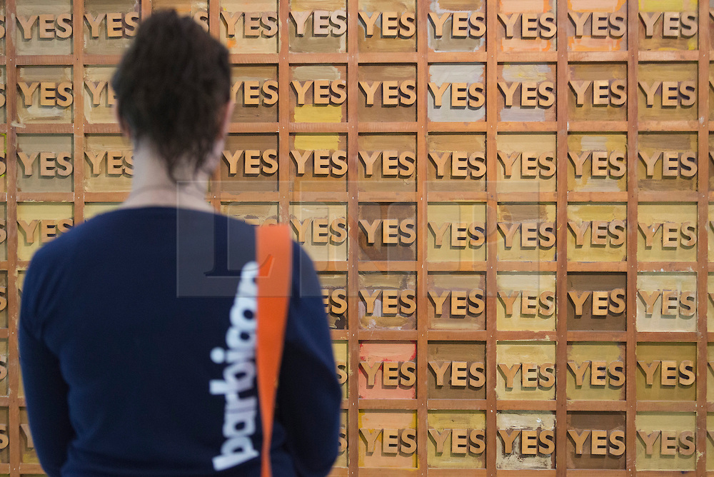 """© Licensed to London News Pictures. 21/10/2013. London, England. A museum workers stands in front of the artwork Joe Tilson, Page 1, 1969.  The Exhibition """"Pop Art Design"""" opens at the Barbican Art Gallery/Barbican Centre running from 22 October 2013 to 9 February 2014. The exhibition brings together 200 works by 70 artists and designers including Peter Blake, Andy Warhol and Roy Lichtenstein. Photo credit: Bettina Strenske/LNP"""