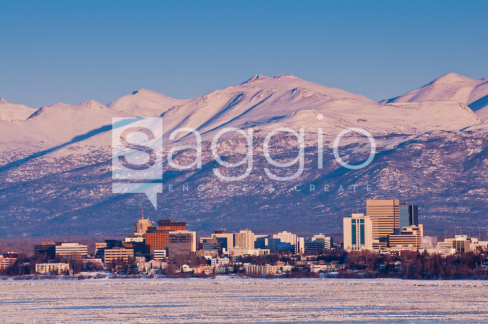 Alpenglow hits the top of the Chugach Mountains as the sun sets on the snow covered city of Anchorage.
