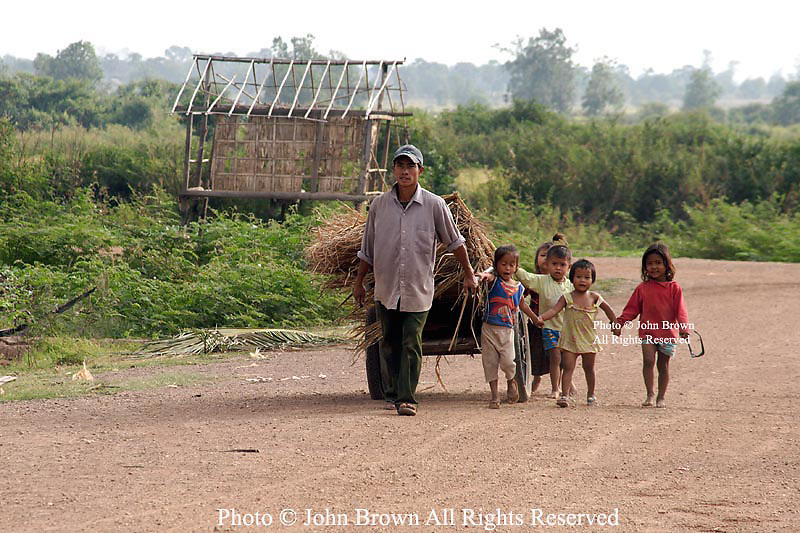 Children accompany a farmer as he walks down a dirt road in Kratie, Cambodia.