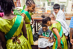 "All Saints competitors look at their pictures in the Daily News from their reception at VICA the night before the competition.  Dancing Classrooms Virgin Islands students compete in ""Colors of the Rainbow"" team match competition at Reichhold Center for the Arts.  St. Thomas, USVI.  9 May 2015.  © Aisha-Zakiya Boyd"