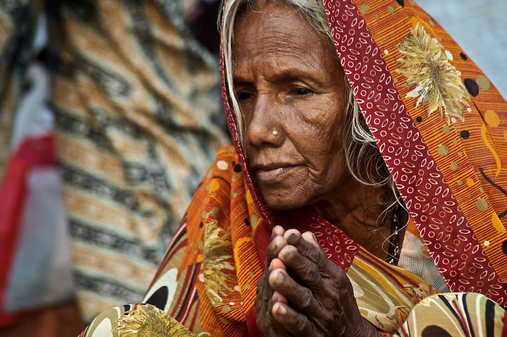 An older woman, a pilgrim to the Hindu holy city of Varanasi, folds her hands in prayer.