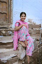 Young lady relazing on the steps in front of her home in Jodhpur, India. Photo taken while traveling in Rajasthan, India, with Steve McCurry.