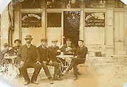 men posing in front of there local cafe
