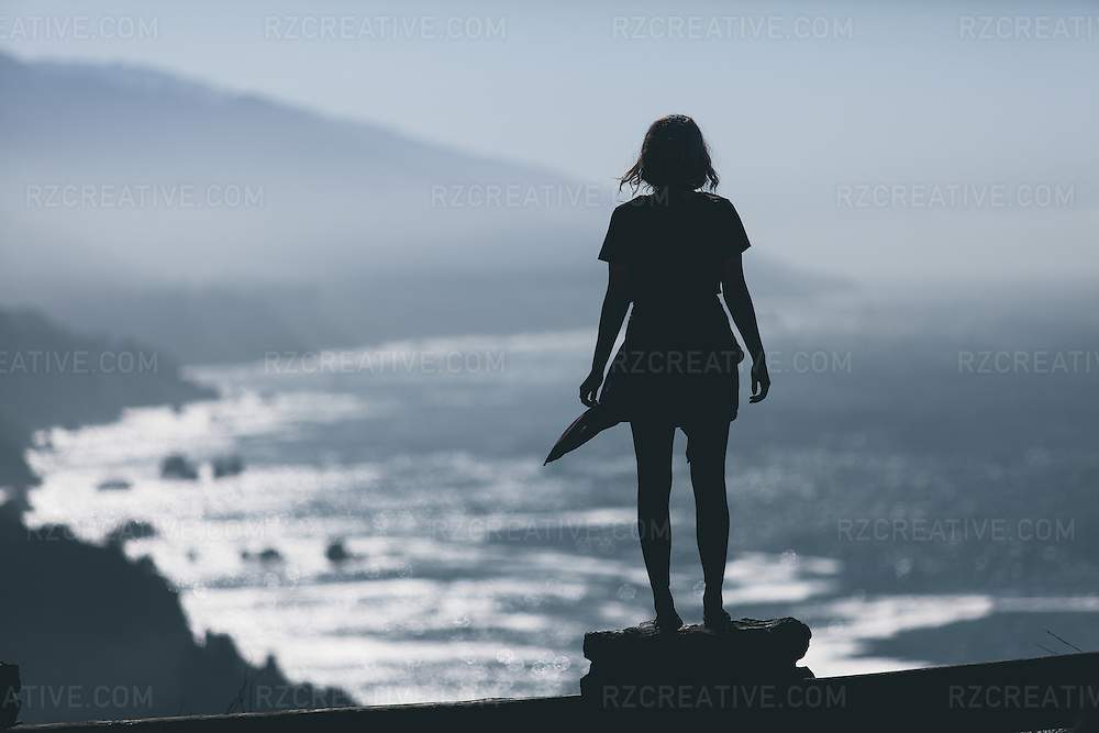 A woman looks out at the moutainous terrain along the rocky coast.