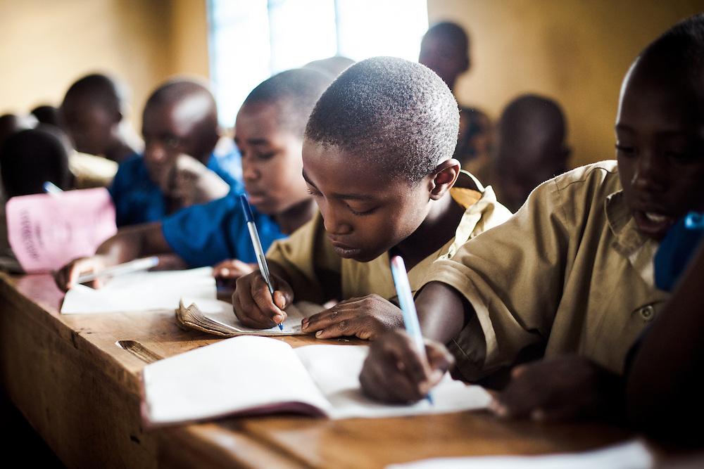 Eriea, 10, (centre), on of Beatrice's children attends class at his local school, Nyamurimirwa. Shingiro District, Rwanda