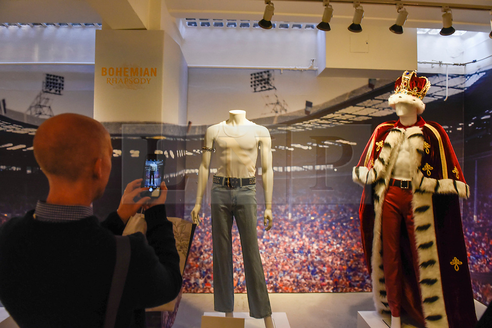 """© Licensed to London News Pictures. 18/10/2018. LONDON, UK. A visitor views stage costumes on display. A Queen pop-up shop has opened in Carnaby Street.  Coinciding with the release next week of the movie """"Bohemian Rhapsody"""", the shop offers Queen music fans memorabilia, a display of stage costumes as well as archived Queen performance footage.  Photo credit: Stephen Chung/LNP"""