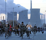 """Scores of factory workers cycyle home after the working day at""""Baogang"""", or Baotou Iron and Steel in northern China December 2, 2003."""