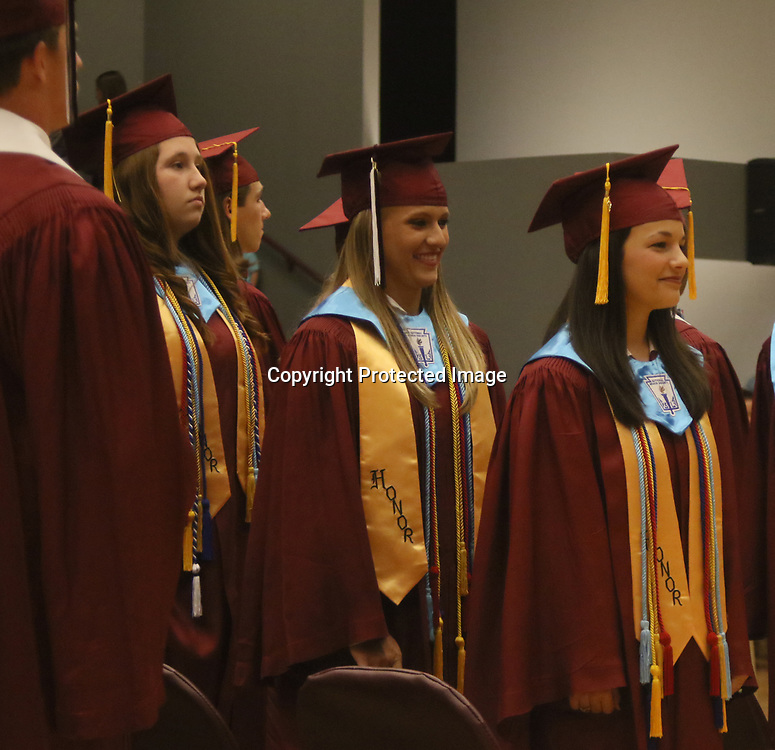 From left, Ashley Bennett, Angel Guyton and Cassidy Herren prepare to receive their diplomas during Smithville's graduation ceremony.