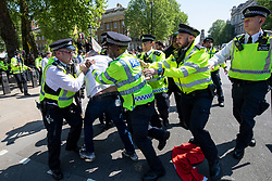 © Licensed to London News Pictures. 15/05/2018. London, UK. An anti-Erdogan protester is arrested in Whitehall ahead of the arrival of Turkish President Recep Tayyip Erdogan to Downing Street. President Erdogan will meet with British Prime Minister Theresa May later. Photo credit: Rob Pinney/LNP
