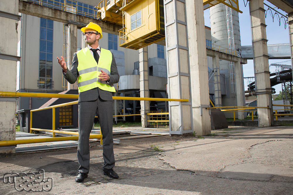 Full length of young male architect gesturing outside industry