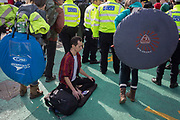 As environmental activists protest about Climate Change during the occupation of City Airport (London's Business Travel hub) in east London, a young man sits in the Lotus Position outside the terminal building on the fourth day of a two-week prolonged worldwide protest by members of Extinction Rebellion, on 10th October 2019, in London, England.