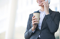 Midsection of businesswoman using cell phone while holding disposable cup outdoors