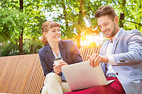Businessman discussing plans over laptop with beautiful businesswoman while sitting on bench