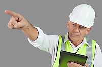 Portrait of male construction worker with tablet PC pointing over gray background
