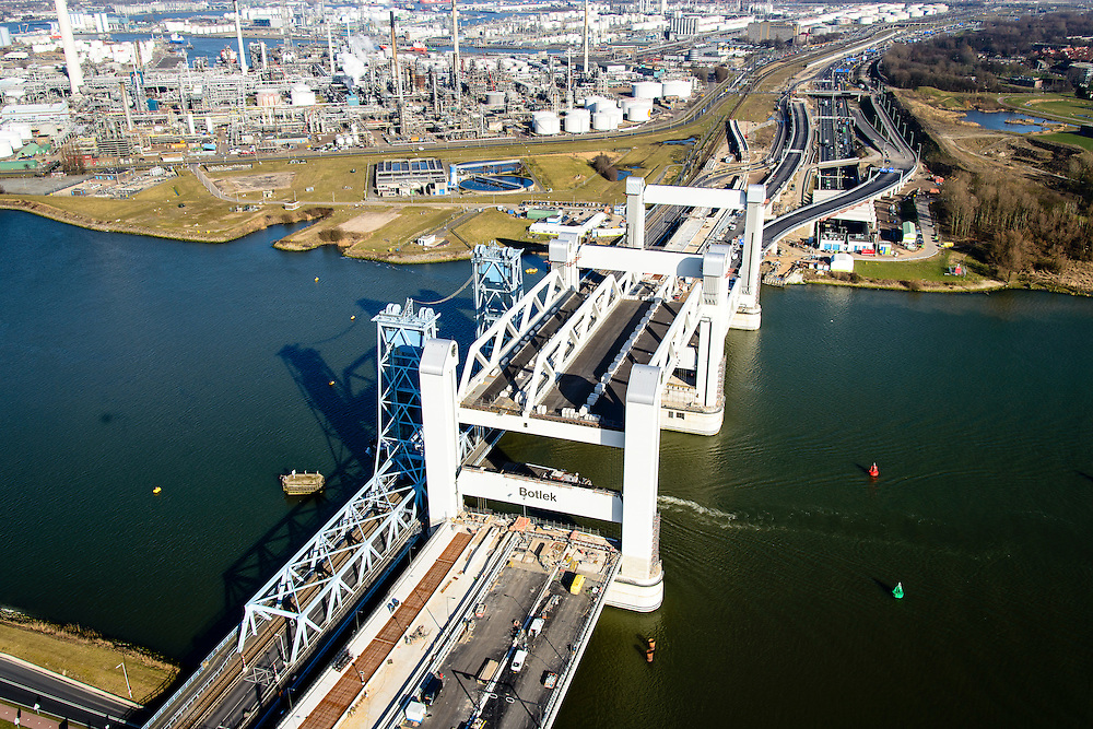 Nederland, Zuid-Holland, Rotterdam, 18-02-2015; bouw van de nieuwe Botlekbrug. De brug over de Oude Maas is een hefbrug, een van de twee brugdelen in geheven toestand. Links de oude brug, raffianderij van Shell Pernis in de achtergrond.<br /> Construction of the new Botlek bridge.<br /> The bridge over the Oude Maas is a vertical-lift bridge or lift bridge, one of the two bridge sections raised. <br /> luchtfoto (toeslag op standard tarieven);<br /> aerial photo (additional fee required);<br /> copyright foto/photo Siebe Swart