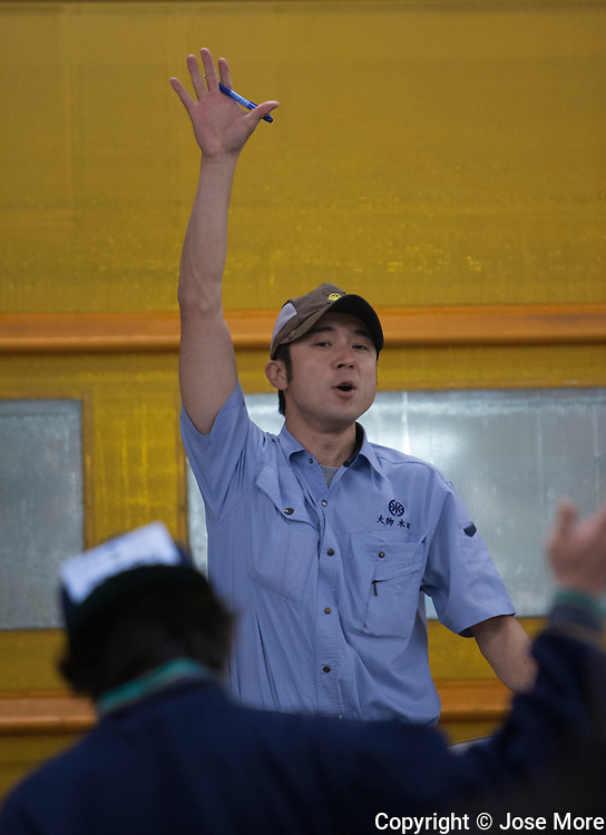 Tokyo, Japan: An auctioneer conducts a tuna fish auction as fish buyers make their bids. The Tokyo Metropolitan Central Wholesale Market, commonly known as the Tsukiji Market, is the largest wholesale fish and seafood market in the world. <br />  Photograph by Jose More