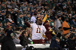 Behind the end zone a Redskin fan with DeSean Jacksons number eleven jersey celebrates amongst eagles fans.