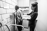 Physician assistant Jen Vaupel checks Robert Young's weight before a check up at Bread for the City in Washington, DC.
