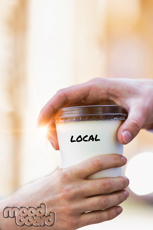 Close up photo of businesswoman giving businessman a cup of local coffee