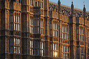 The sun reflecting in the windows of the Palace of Westminster, also known as the Houses of Parliament or Westminster Palace.  It is the meeting place of the two houses of the Parliament of the United Kingdom and is on the bank of the river Thames in London.